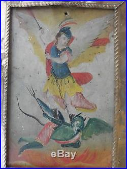 Saint Michael Defeating Lucifer' folk art icon, oil on metal, in curio cabinet